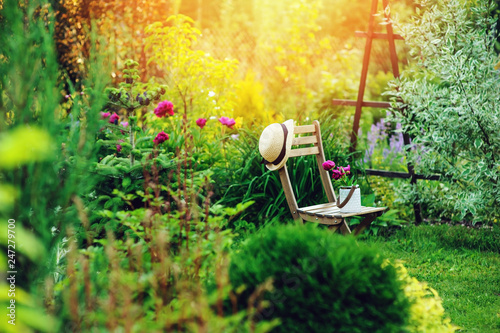 Poster Garden beautiful blooming summer private garden with wooden chair, gardener hat and watering can