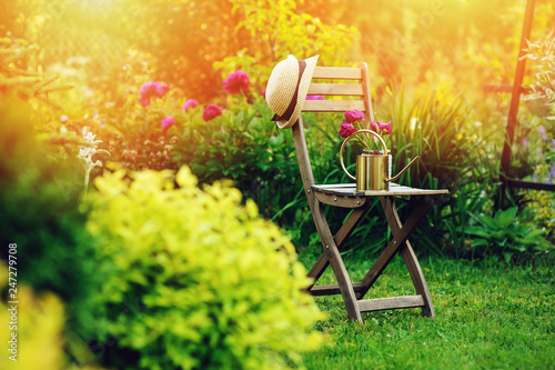 Papiers peints Jardin beautiful blooming summer private garden with wooden chair, gardener hat and watering can