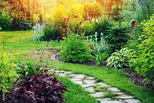 Spoed Fotobehang Tuin beautiful summer cottage garden view with stone pathway and blooming perennials