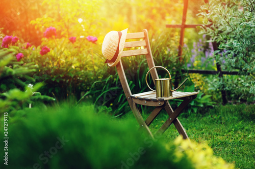 Foto op Plexiglas Groene beautiful blooming summer private garden with wooden chair, gardener hat and watering can