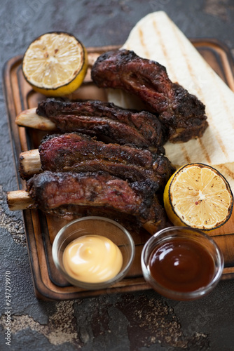 Close-up of bbq beef ribs with dipping sauces, lemon and tortillas, selective focus, vertical shot