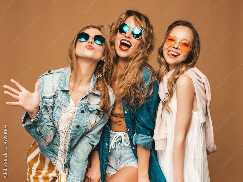 Fototapeta Three beautiful smiling hipster girls in trendy summer casual clothes and sunglasses. Sexy carefree women posing near golden wall. Positive models going crazy. Showing tongue