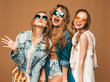 Three beautiful smiling hipster girls in trendy summer casual clothes and sunglasses. Sexy carefree women posing near golden wall. Positive models going crazy. Showing tongue