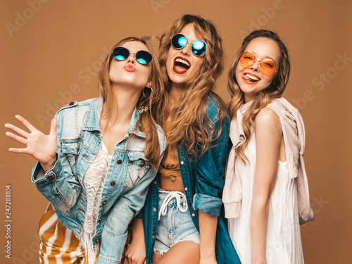 Three beautiful smiling hipster girls in trendy summer casual clothes and sunglasses. Sexy carefree women posing near golden wall. Positive models going crazy. Showing tongue - fototapety na wymiar