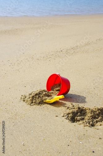 Fotografie, Obraz  砂遊び 赤いバケツとスコップ 夏休み