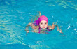 Portrait of cute smiling little girl child swimmer in pink swimming suit and cap in the swimming poo