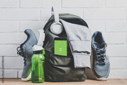 Poster Fitness Green backpack with sportswear and sneakers. The concept of fitness or running