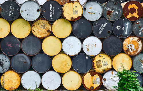 Fotografie, Obraz  Many old, rusty drums, partially with 'Ethyl Acetate' signage on it, piled up orderly in many rows