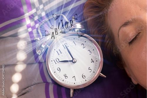 Foto  Eine Frau im Bett, Wecker und Hinweis auf Abitur
