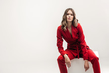 Vogue Model Seating On White Cube In Red Elegant Suit
