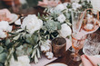 canvas print picture - on wooden banquet table are glasses, plates, candles, table is decorated with compositions of cotton and eucalyptus branches