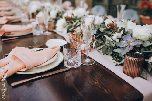 Fototapeta on wooden banquet table are glasses, candles, table is decorated with compositions of cotton and eucalyptus branches, plates are decorated with napkins and sprig of greenery obraz
