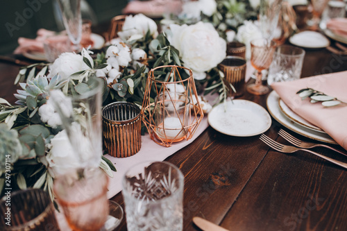 Photo on wooden banquet table are glasses, plates, candles, table is decorated with co