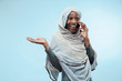 Leinwanddruck Bild - The beautiful young black african muslim girl wearing gray hijab at blue studio. She standing with mobile phone with a happy smile on her face. The human emotions, facial expression concept. Trendy