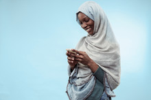 The Beautiful Young Black African Muslim Girl Wearing Gray Hijab At Blue Studio. She Standing With Mobile Phone With A Happy Smile On Her Face. The Human Emotions, Facial Expression Concept. Trendy