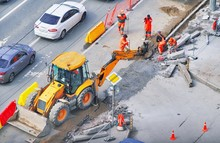 Bulldozer With Group Of Workers Wear Safety Uniform During Road Works In An Asphalt Road. New Kerb Stones On Gravel Ground Placing Road Edge At Construction Site. Machine Labor Builder Digging Highway
