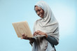 canvas print picture - Portrait Of Female University Student Working on laptop. The beautiful young black african muslim girl wearing gray hijab at blue studio. She standing with happy smile on her face.