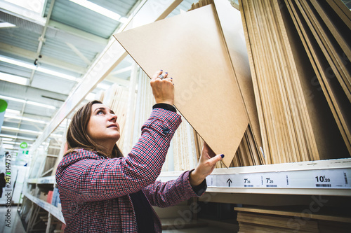 Fotografiet  Woman at home building material choosing wood to renovate her home