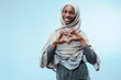 Leinwanddruck Bild - The beautiful young black african muslim girl wearing gray hijab at blue studio. She standing with a happy smile on her face. The human emotions, facial expression concept. Trendy colors