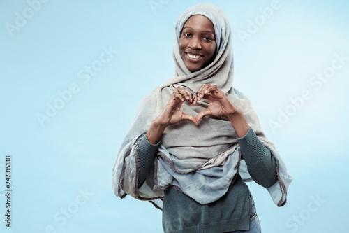 Fotografia The beautiful young black african muslim girl wearing gray hijab at blue studio