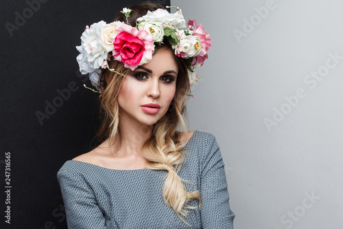 Fotografie, Obraz  closeup portrait of beautiful attractive fashion model in grey dress with makeup, hairstyle and head flowers on her head, looking at camera