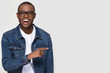 Happy excited african man customer laughing pointing finger aside at copy space, cheerful black guy advertising fun optics denim shop or dental service sale offer isolated on white studio background