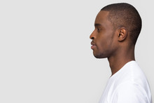 Millennial African American Man Standing In Profile Isolated On Blank White Grey Studio Background, Confident Black Guy Looking Forward At Copy Space Thinking Of Future Leadership, Side View Portrait
