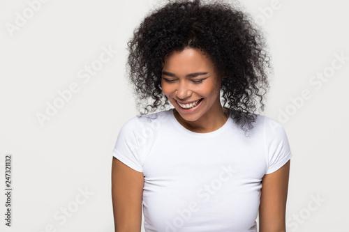 Fotografie, Obraz  Cheerful black girl laughing at funny joke isolated on white grey blank studio b