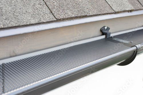 Canvas Print Plastic guard over new dark grey plastic rain gutter on asphalt shingles roof at shallow depth of field