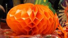Orange Halloween Pumpkin Paper Mache Decoration On Table With People Walking Behind 4K