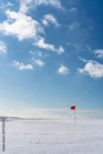 Valokuva  Snow covered deserted golf green with red flag, on Cleeve Hill, Cotswolds, Glouc
