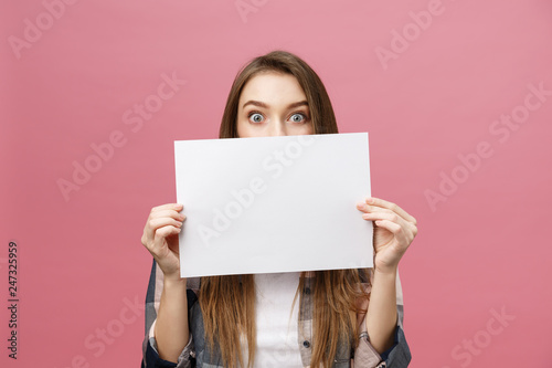 Obraz Young caucasian woman holding blank paper sheet over isolated background scared in shock with a surprise face, afraid and excited with fear expression - fototapety do salonu