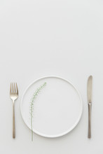 Minimal Grey And White Table Setting With A Brass Cutlery Set, A Plate Decorated With Greenery.