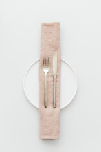 Minimal Grey And White Table Setting With A Brass Cutlery Set, A Plate And A Pink Napkin.