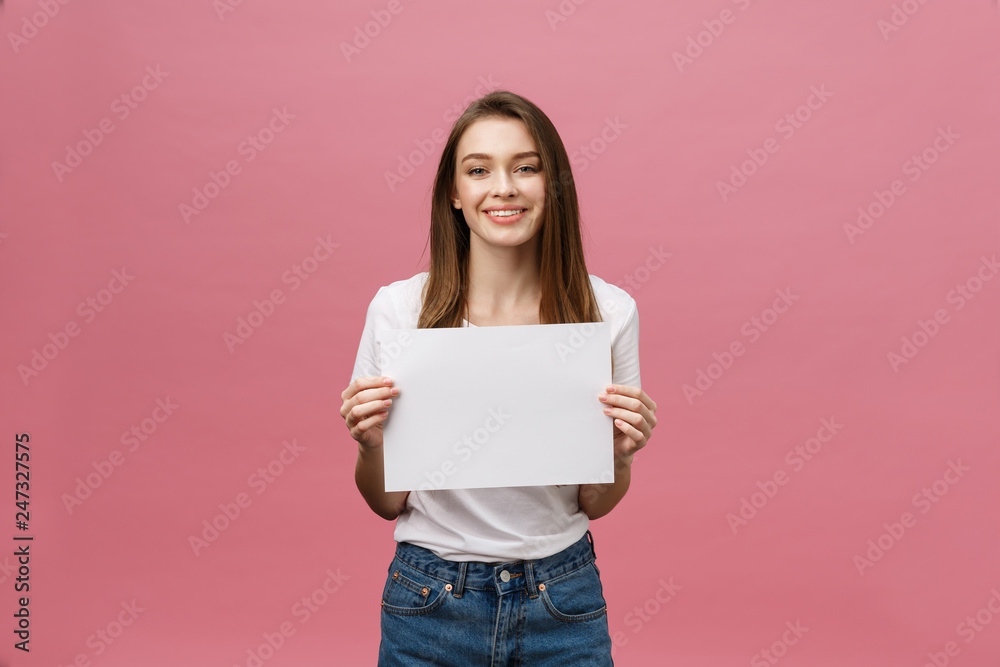 Fototapeta Close up portrait of positive laughing woman smiling and holding white big mockup poster isolated on pink background