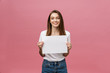 canvas print picture - Close up portrait of positive laughing woman smiling and holding white big mockup poster isolated on pink background