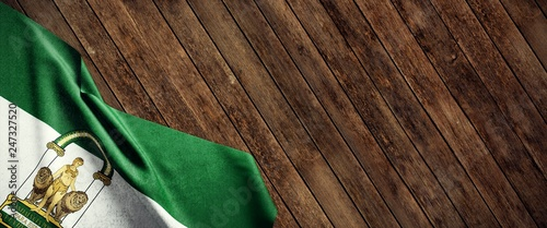 Bandera de Andalucía sobre fondo de madera
