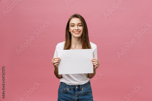 Obraz Close up portrait of positive laughing woman smiling and holding white big mockup poster isolated on pink background - fototapety do salonu