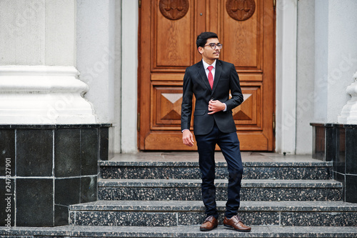7b509181962d Indian young man at glasses, wear on black suit with red tie posed outdoor  against
