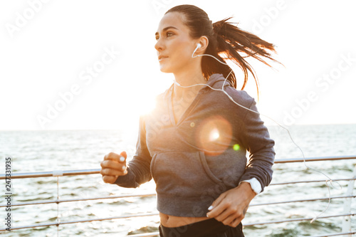Young sports fitness woman running at the beach outdoors. - 247331935
