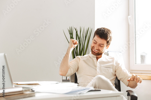 fototapeta na lodówkę Photo of handsome businessman 30s wearing white shirt rejoicing, while working in bright office