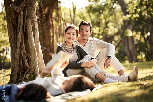 asian family with two children relaxing in park - 247348791
