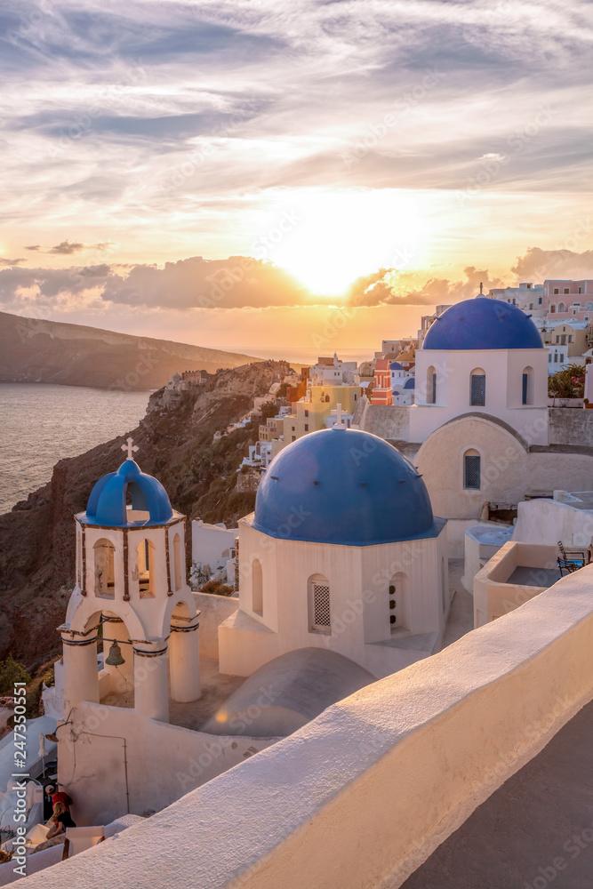 Fototapeta Oia village with churches against sunset on Santorini island in Greece