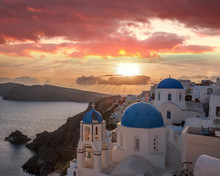 Oia Village With Churches Against Sunset On Santorini Island In Greece