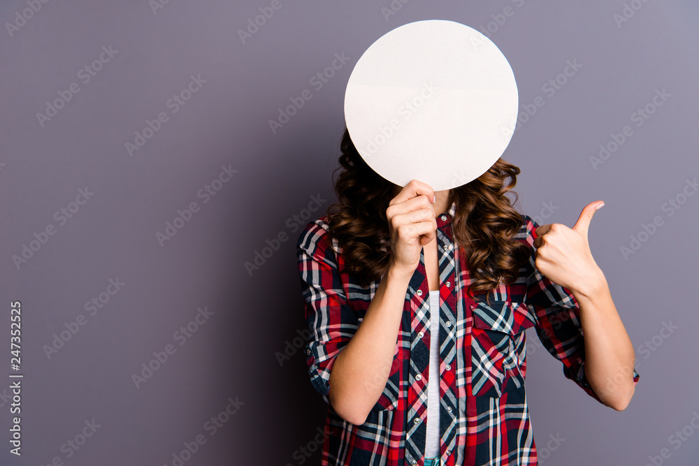 Fototapeta Close up portrait of unknown beautiful amazing she her lady arm show hold round card hide facial expression behind thumb up anonymous vote wear casual checkered plaid shirt isolated grey background