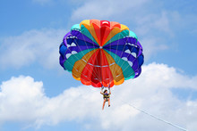 Tiny Happy Girl On Colorful Parasail In The Blue Sky