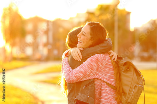 Fotografie, Obraz  Happy friends meeting and hugging in a park at sunset
