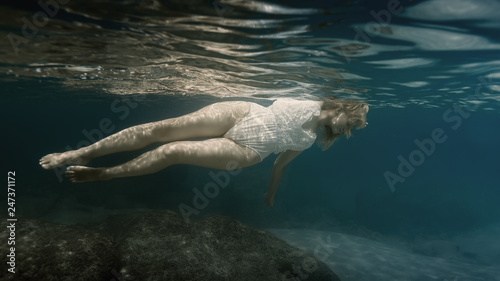Woman in white under water in the sea Canvas Print