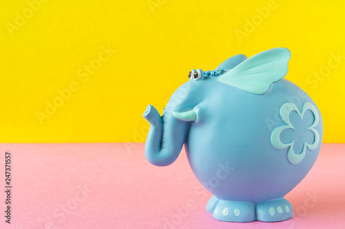 Fotografia  Funny blue toy elephant. On a yellow-pink background.