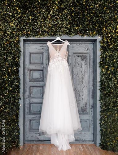 Cuadros en Lienzo White wedding dress of bride hangs on background of door, boho and rustic style